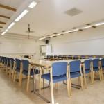 Stort konferensrum med projektor och högtalarsystem.